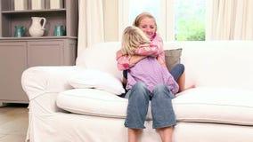 Χαριτωμένη συνεδρίαση μικρών κοριτσιών με τη μητέρα στον καναπέ απόθεμα βίντεο