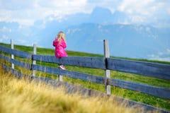 Χαριτωμένη συνεδρίαση μικρών κοριτσιών στον ξύλινο φράκτη που θαυμάζει το όμορφο τοπίο στη σειρά βουνών δολομιτών Στοκ φωτογραφία με δικαίωμα ελεύθερης χρήσης