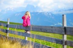 Χαριτωμένη συνεδρίαση μικρών κοριτσιών στον ξύλινο φράκτη που θαυμάζει το όμορφο τοπίο στη σειρά βουνών δολομιτών Στοκ Εικόνες