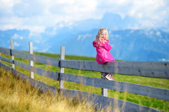 Χαριτωμένη συνεδρίαση μικρών κοριτσιών στον ξύλινο φράκτη που θαυμάζει το όμορφο τοπίο στη σειρά βουνών δολομιτών Στοκ εικόνα με δικαίωμα ελεύθερης χρήσης