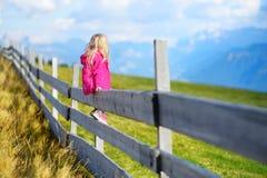 Χαριτωμένη συνεδρίαση μικρών κοριτσιών στον ξύλινο φράκτη που θαυμάζει το όμορφο τοπίο στη σειρά βουνών δολομιτών Στοκ φωτογραφίες με δικαίωμα ελεύθερης χρήσης