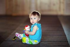 Χαριτωμένη συνεδρίαση μικρών κοριτσιών στο πάτωμα και εκμετάλλευση ένα CL Santa παιχνιδιών Στοκ Εικόνα