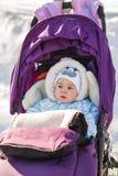 Χαριτωμένη συνεδρίαση μωρών χαμόγελου στον περιπατητή μια κρύα χειμερινή ημέρα Στοκ Εικόνες