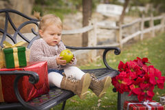 Χαριτωμένη συνεδρίαση παιδιών μικρών παιδιών στον πάγκο με τα δώρα Χριστουγέννων έξω Στοκ εικόνα με δικαίωμα ελεύθερης χρήσης