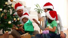 Χαριτωμένη συνεδρίαση δώρων οικογενειακών ανοίγοντας Χριστουγέννων στο πάτωμα απόθεμα βίντεο