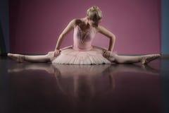 Χαριτωμένη συνεδρίαση ballerina με τα πόδια που τεντώνονται έξω στοκ εικόνα