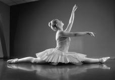 Χαριτωμένη συνεδρίαση ballerina με τα πόδια που τεντώνονται έξω στοκ εικόνες