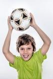 Χαριτωμένη σφαίρα εκμετάλλευσης παιδιών ποδοσφαίρου χαμόγελου επάνω από το κεφάλι του στοκ εικόνες