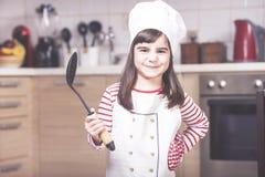 Χαριτωμένη τοποθέτηση αρχιμαγείρων μικρών κοριτσιών στην κουζίνα Στοκ Φωτογραφία