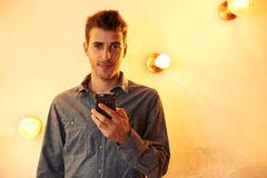 Χαριτωμένη τοποθέτηση νεαρών άνδρων με το κινητό τηλέφωνο Στοκ εικόνα με δικαίωμα ελεύθερης χρήσης
