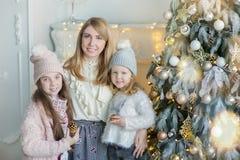 Χαριτωμένη τρομερή ξανθή μητέρα mom με δύο κόρες κοριτσιών που γιορτάζουν τα νέα Χριστούγεννα έτους κοντά στο σύνολο χριστουγεννι Στοκ φωτογραφία με δικαίωμα ελεύθερης χρήσης