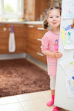 Χαριτωμένη τσίχλα μικρών κοριτσιών πίσω από την πόρτα ψυγείων στην κουζίνα Στοκ εικόνα με δικαίωμα ελεύθερης χρήσης