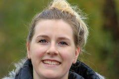 Χαριτωμένη φυσική ξανθή γυναίκα που χαμογελά με τα τέλεια άσπρα δόντια και το καμμένος δέρμα στοκ φωτογραφίες
