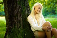 Χαριτωμένη φυσική χαλάρωση ομορφιάς ενάντια σε ένα δέντρο Στοκ Εικόνες
