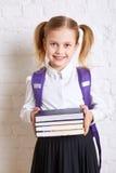Χαριτωμένη χαμογελώντας μαθήτρια στην ομοιόμορφη στάση με τα βιβλία και το χαμόγελο Στοκ Φωτογραφίες