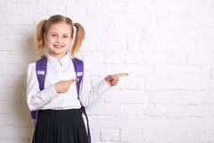 Χαριτωμένη χαμογελώντας μαθήτρια στην ομοιόμορφη στάση στο ελαφρύ υπόβαθρο και την παρουσίαση αντίχειρων στην πλευρά Στοκ Εικόνα