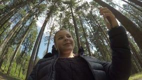 Χαριτωμένη χιλιετής χαλάρωση γυναικών σε ένα δασικό smartphone χρησιμοποίησης κινητό για το πυροβολισμό φωτογραφιών selfie - φιλμ μικρού μήκους