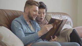 Χαριτωμένη όμορφη γιαγιά και ενήλικη συνεδρίαση εγγονών στο σπίτι στον καφετή καναπέ δέρματος που προσέχει τις παλαιές φωτογραφίε απόθεμα βίντεο