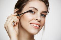 Χαριτωμένη όμορφη εξέταση χαμόγελου χρωστικών ουσιών κοριτσιών eyelashes τη κάμερα πέρα από το άσπρο υπόβαθρο Υγεία και cosmetolo Στοκ εικόνα με δικαίωμα ελεύθερης χρήσης