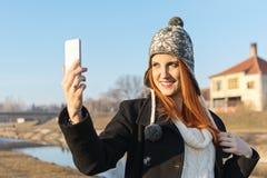 Χαριτωμένη redhead νέα γυναίκα που παίρνει ένα selfie στοκ φωτογραφίες