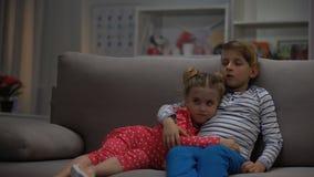 Χαριτωμένοι αδελφός και αδελφή που αγκαλιάζουν τον κινηματογράφο προσοχής καναπέδων, ελεύθερος χρόνος συσκευών, τηλεόραση φιλμ μικρού μήκους