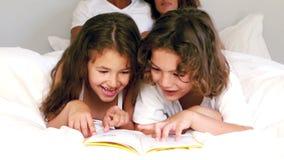 Χαριτωμένοι αμφιθαλείς που διαβάζουν ένα βιβλίο στο κρεβάτι γονέων τους φιλμ μικρού μήκους