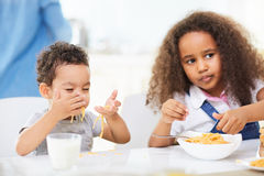 Χαριτωμένοι αδελφός και αδελφή που τρώνε τα ζυμαρικά Στοκ εικόνα με δικαίωμα ελεύθερης χρήσης