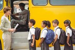 Χαριτωμένοι μαθητές που περιμένουν να πάρει στο σχολικό λεωφορείο Στοκ Εικόνες