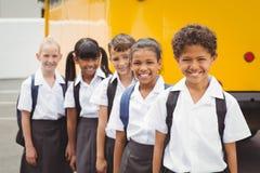 Χαριτωμένοι μαθητές που χαμογελούν στη κάμερα με το σχολικό λεωφορείο Στοκ φωτογραφία με δικαίωμα ελεύθερης χρήσης