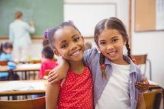 Χαριτωμένοι μαθητές που χαμογελούν στη κάμερα στην τάξη Στοκ Φωτογραφία