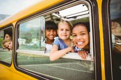 Χαριτωμένοι μαθητές που χαμογελούν στη κάμερα στο σχολικό λεωφορείο Στοκ φωτογραφία με δικαίωμα ελεύθερης χρήσης