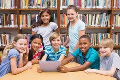 Χαριτωμένοι μαθητές που χρησιμοποιούν τον υπολογιστή ταμπλετών στη βιβλιοθήκη Στοκ φωτογραφία με δικαίωμα ελεύθερης χρήσης