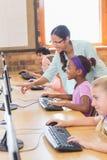 Χαριτωμένοι μαθητές στην κατηγορία υπολογιστών με το δάσκαλο Στοκ Εικόνες