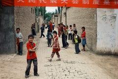 χαριτωμένοι νεαροί που πηγαίνουν στο σπίτι μετά από το σχολείο σε ένα κινεζικό χωριό στοκ φωτογραφία