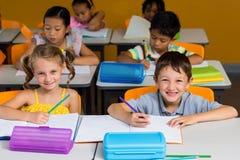 Χαριτωμένοι συμμαθητές που χαμογελούν στην τάξη στοκ εικόνες