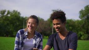 Χαριτωμένοι φίλοι που στηρίζονται σε ένα πάρκο, το κάθισμα στη χλόη, την εξέταση το smartphone και το γέλιο Μικτή συνεδρίαση ζευγ απόθεμα βίντεο