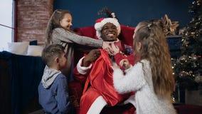 Χαριτωμένος Άγιος Βασίλης στην τσάντα ανοίγματος καπέλων με τα δώρα για τα παιδιά φιλμ μικρού μήκους