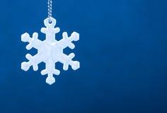 Χαριτωμένος άσπρος ανακλαστήρας ασφάλειας υπό μορφή snowflakes στο μπλε υπόβαθρο Απαραίτητος εξοπλισμός στους πεζούς για τους περ στοκ εικόνες