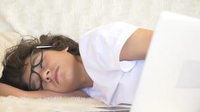 Χαριτωμένος έφηβος αγοριών που φορά τους ύπνους γυαλιών στον καναπέ δίπλα στο lap-top 4K φιλμ μικρού μήκους