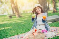 Χαριτωμένος έφηβος που δίνει τα φρούτα για την κατανάλωση των υγιών τροφίμων όταν πικ-νίκ στοκ εικόνες