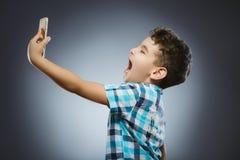 Χαριτωμένος έφηβος που παίρνει selfie στο γκρίζο υπόβαθρο Στοκ φωτογραφίες με δικαίωμα ελεύθερης χρήσης