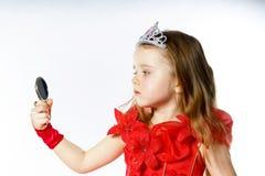 Χαριτωμένος λίγη πριγκήπισσα που ντύνεται στο κόκκινο στο άσπρο υπόβαθρο Στοκ Εικόνα
