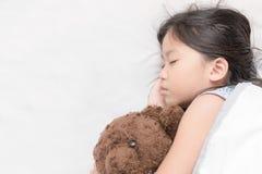 Χαριτωμένος λίγοι ασιατικοί ύπνος και αγκάλιασμα κοριτσιών teddy αντέχουν Στοκ φωτογραφία με δικαίωμα ελεύθερης χρήσης