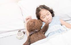 Χαριτωμένος λίγοι ασιατικοί ύπνος και αγκάλιασμα κοριτσιών teddy αντέχουν Στοκ Φωτογραφία