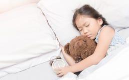 Χαριτωμένος λίγοι ασιατικοί ύπνος και αγκάλιασμα κοριτσιών teddy αντέχουν Στοκ Φωτογραφίες