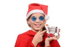 Χαριτωμένος λίγος Άγιος Βασίλης που δίνει την πιστωτική κάρτα και μικρό caddy Στοκ Φωτογραφία