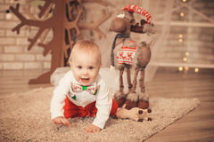Χαριτωμένος λίγο αγοράκι μεταξύ των διακοσμήσεων Χριστουγέννων Στοκ Φωτογραφία