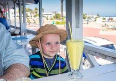Χαριτωμένος λίγο ευτυχές αγόρι που προσδοκά πίνοντας μια μπανάνα milkshake Στοκ φωτογραφίες με δικαίωμα ελεύθερης χρήσης