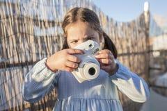 Χαριτωμένος λίγο ευτυχές κορίτσι με τη στιγμιαία κάμερα φωτογραφιών εικόνων στοκ εικόνες