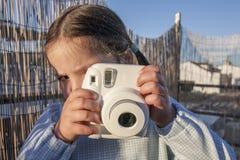 Χαριτωμένος λίγο ευτυχές κορίτσι με τη στιγμιαία κάμερα φωτογραφιών εικόνων στοκ φωτογραφία με δικαίωμα ελεύθερης χρήσης